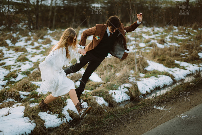 Groom and bride jumping over ditch onto rural road