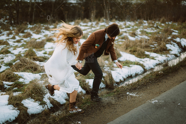Bride and groom jumping over ditch onto rural road