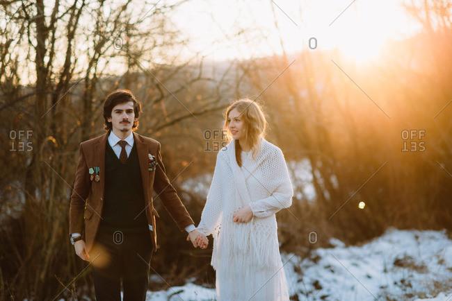 Stylish young bridal couple in sun dappled field