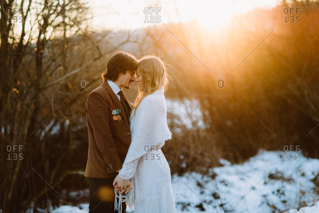 Young bridal couple embracing in sun dappled field