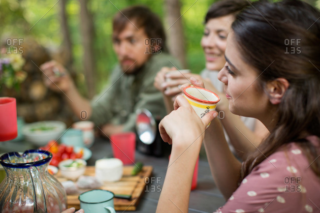 Four people seated around a wooden table outdoors in woodland sharing a meal