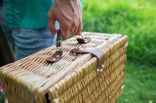 A man's hand holding a wicker picnic basket
