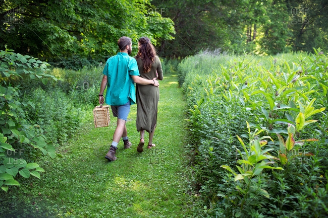 A man and woman walking through a meadow, through the long grass, carrying a picnic basket
