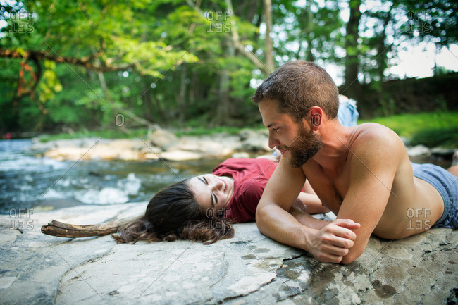 A young man and woman lying on the rocks on a river bank