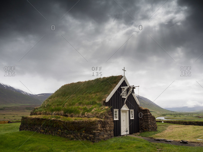 A traditional wooden church with turf roof, earth and grass material on the steep pitched roof
