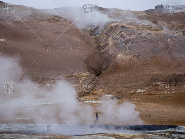 A person walks along the steamy edge of a hot spring