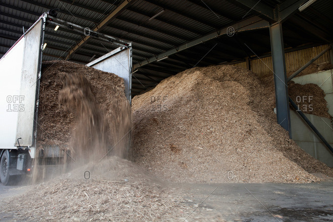 Stored organic waste being poured from a lorry into a large warehouse for biomass fuel production