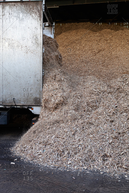 Stored organic waste heaped up in a large warehouse for biomass fuel production
