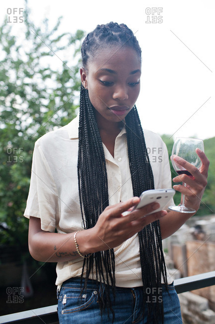 Young woman with cell phone on apartment deck