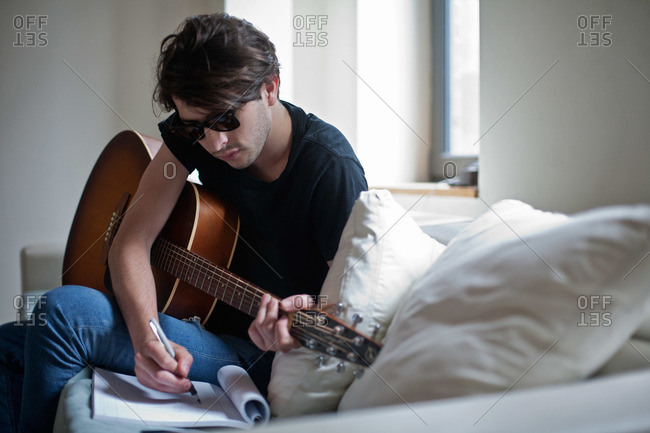Young musician writing songs with acoustic guitar