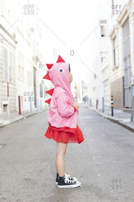 A little girl in a pink dinosaur hoodie in San Francisco, CA