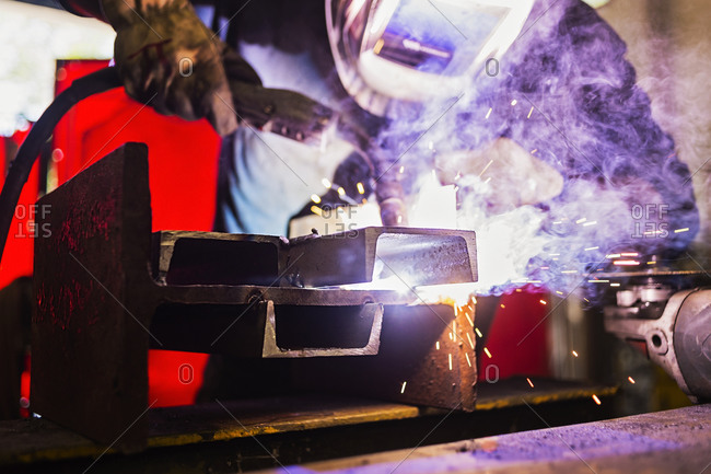 Gleaming piece of metal being welded by worker