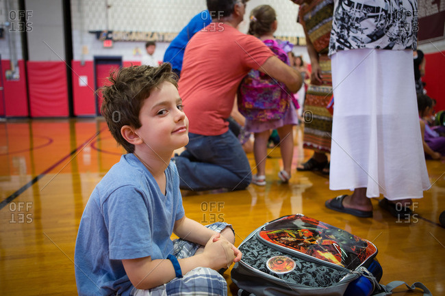 Young boy sitting on school gymnasium floor with his backpack