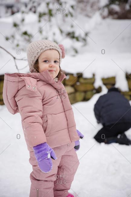 Little girl in pink snowsuit in snowy backyard