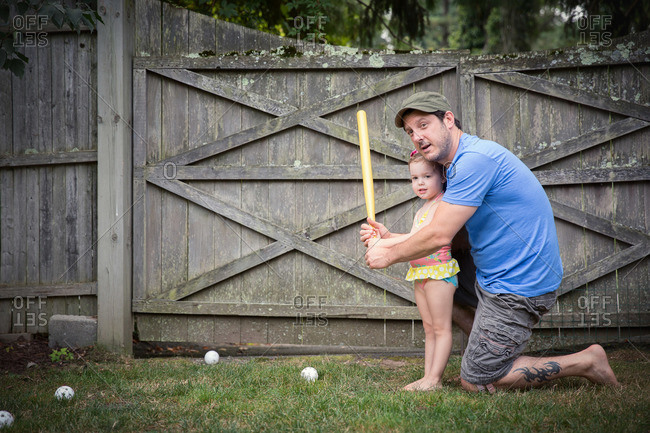 Father stands at bat with his daughter in a game of wiffle ball