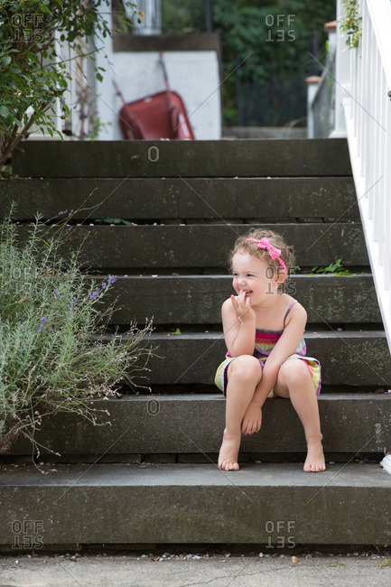 Giggling young girl sitting on steps in garden