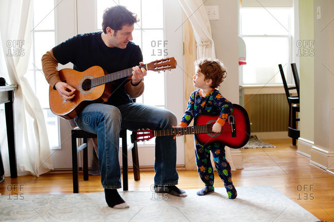Man and young boy playing guitars in living room
