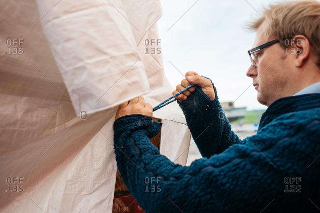 Man tying tarp over a boat