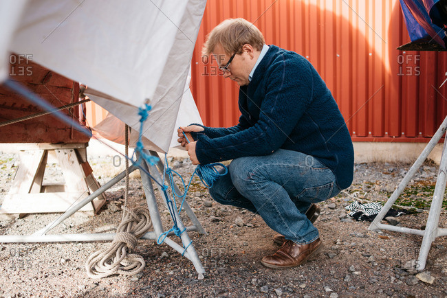 Man fastening a tarp over a boat