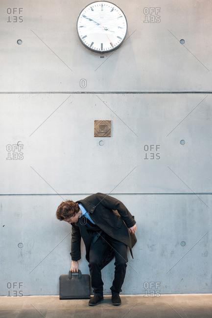 Businessman grabbing briefcase under a clock