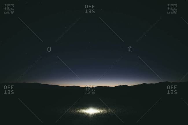 View of Milky Way and night sky, bright glowing light on surface of playa in foreground, Black Rock Desert, Nevada, USA