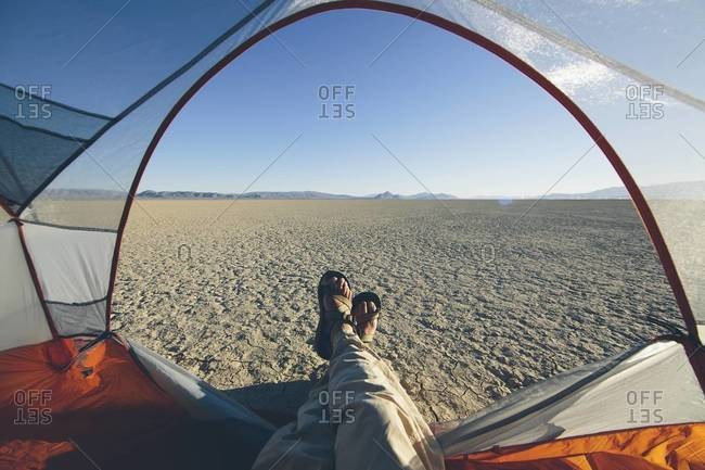 Man in his tent taking in the view of desert and playa in Black Rock Desert, Nevada