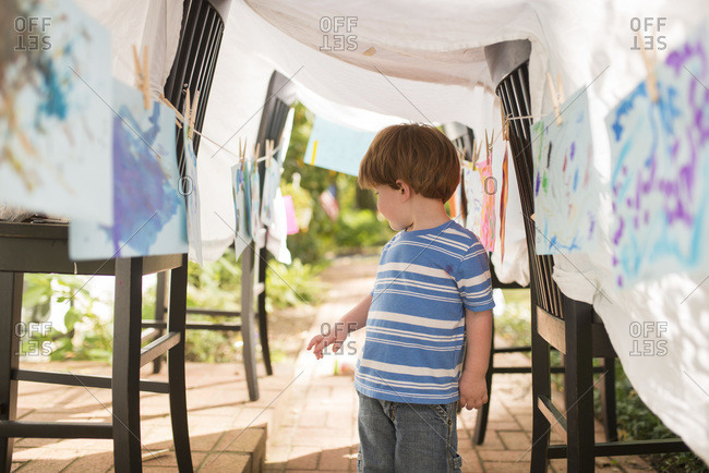 Boy surrounded by his art in pretend art gallery