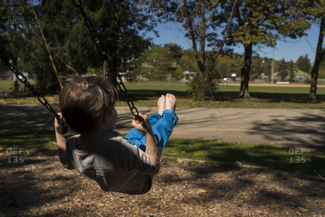 Boy with bare feet on a swing