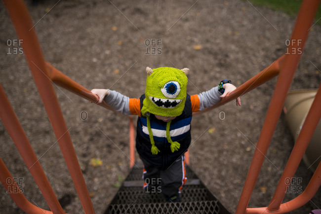 Boy on playground wearing green monster hat