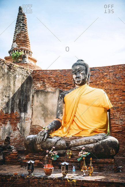 View to ancient Buddha statue covered with yellow cloth, Ayutthaya