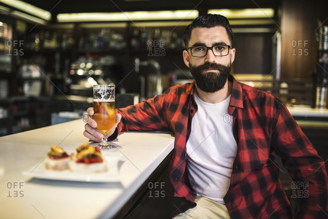 Portrait of hipster with glass of beer and tapas sitting at counter in a pub