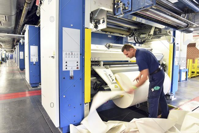 Man working at printing machine in a printing shop