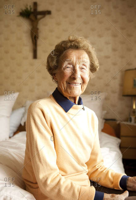 Portrait of aged woman sitting on bed at her bedroom