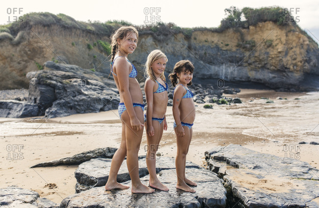 Three girls standing in a row on the beach