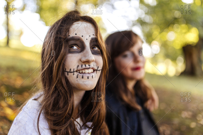 Portrait of masquerade girl at Halloween with her friend in the background