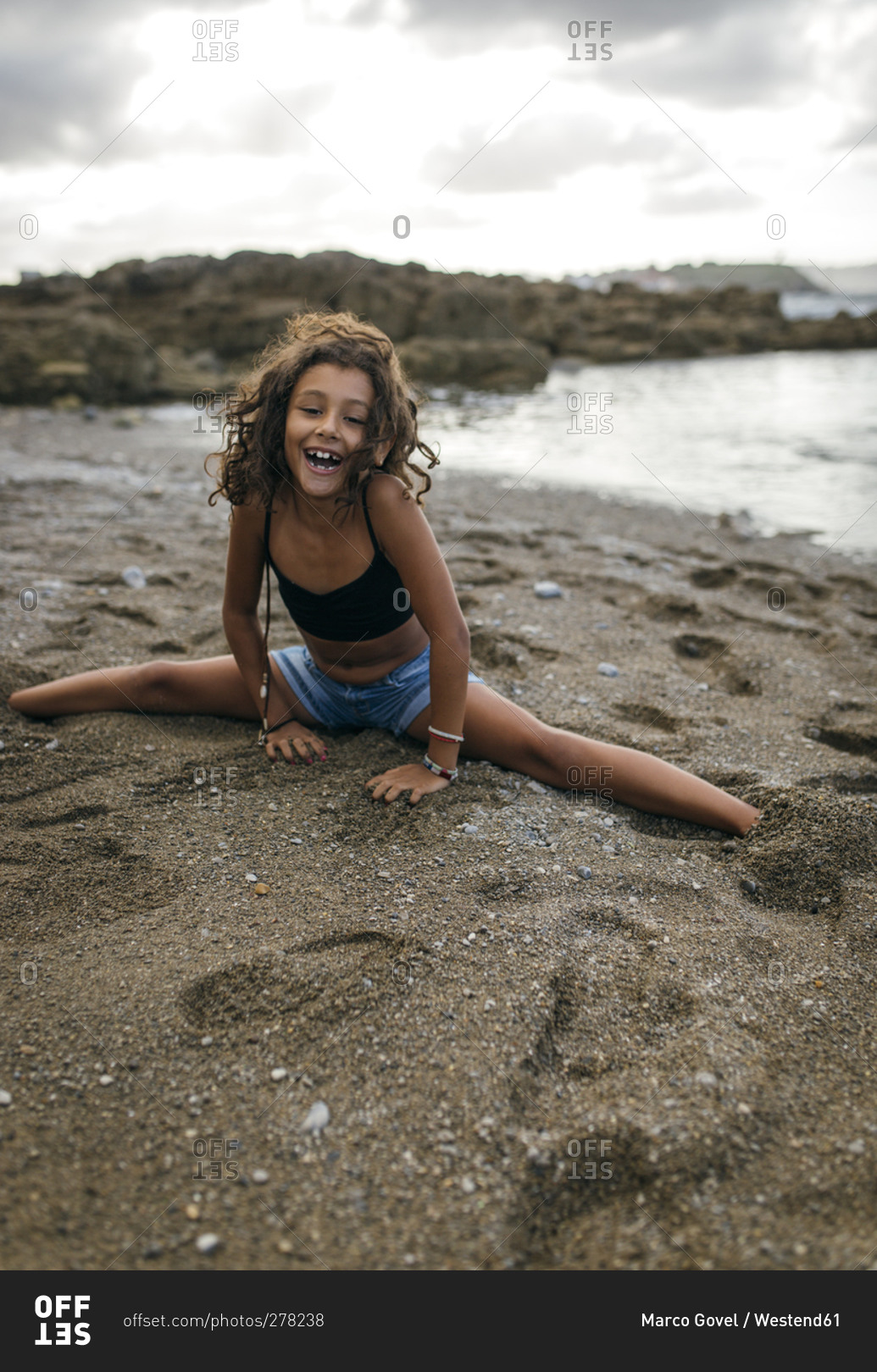 Portrait of smiling little girl doing the splits on a ...