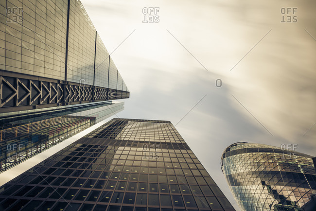 Facades of office towers at financial district seen from below, London