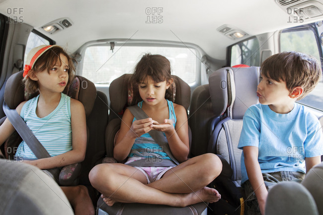 Siblings riding in the backseat of a car