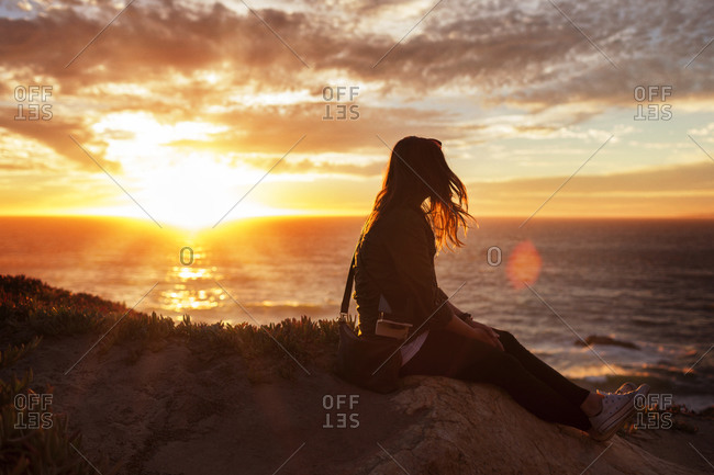 Woman sitting and watching sunset over the ocean