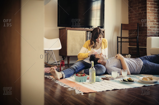 Couple having a picnic on their living room floor