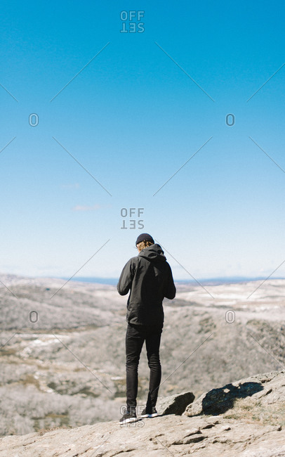 Hip young man on scenic mountain lookout
