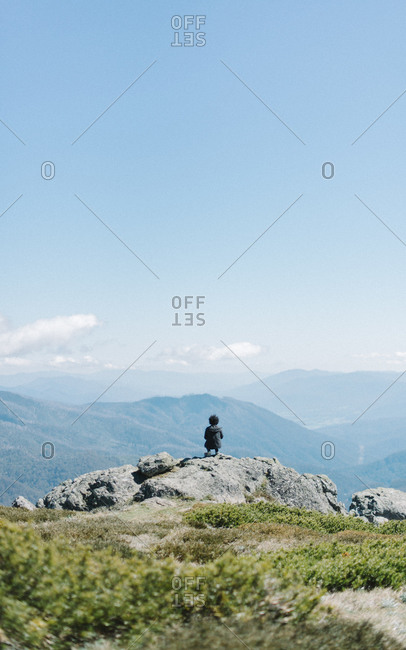 Hip young man kneeling on scenic mountain lookout