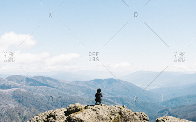 Hip man kneeling on scenic mountain lookout