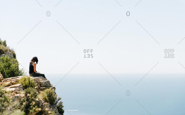 Woman on cliff overlooking the ocean