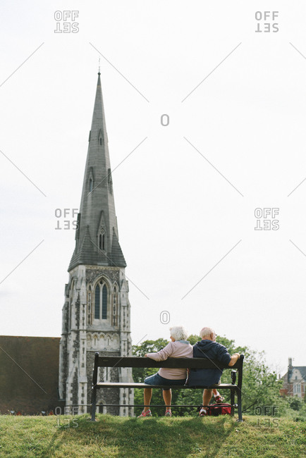 Elderly couple sitting on bench outside a church
