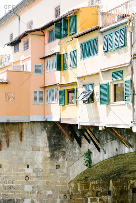 Man looking out window of traditional Italian home