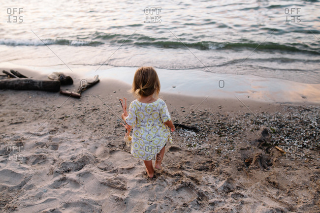 A little girl wanders on the shore