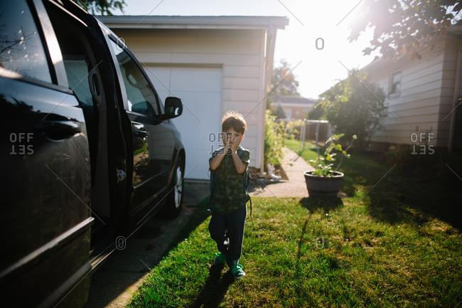 A boy walks towards a minivan