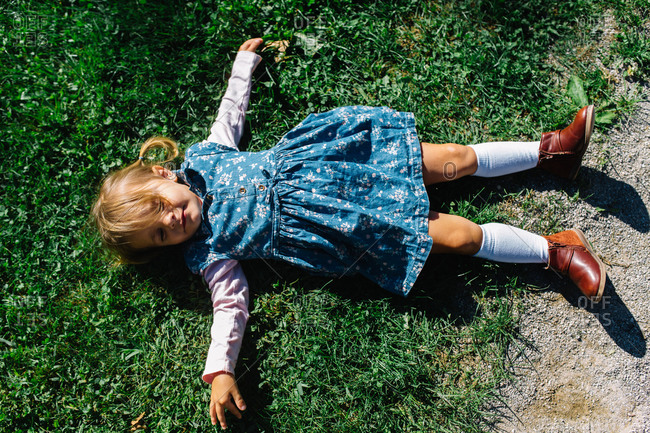 Young girl in dress and knee socks lying on grass in sun