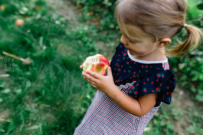 Elevated view of toddler girl eating an apple
